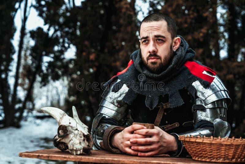 O cavaleiro masculino senta-se em uma tabela de madeira fotos de stock