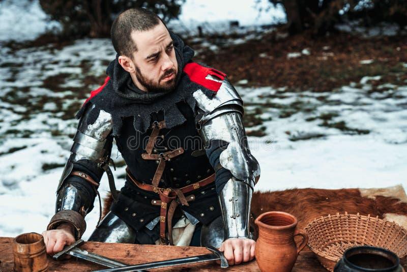 O cavaleiro masculino senta-se em uma tabela de madeira fotografia de stock royalty free