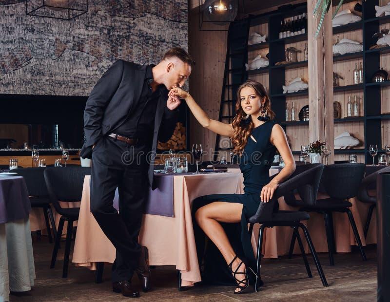 O cavalheiro elegante e considerável beija sua mão amado do ` s durante datar no restaurante fotografia de stock royalty free