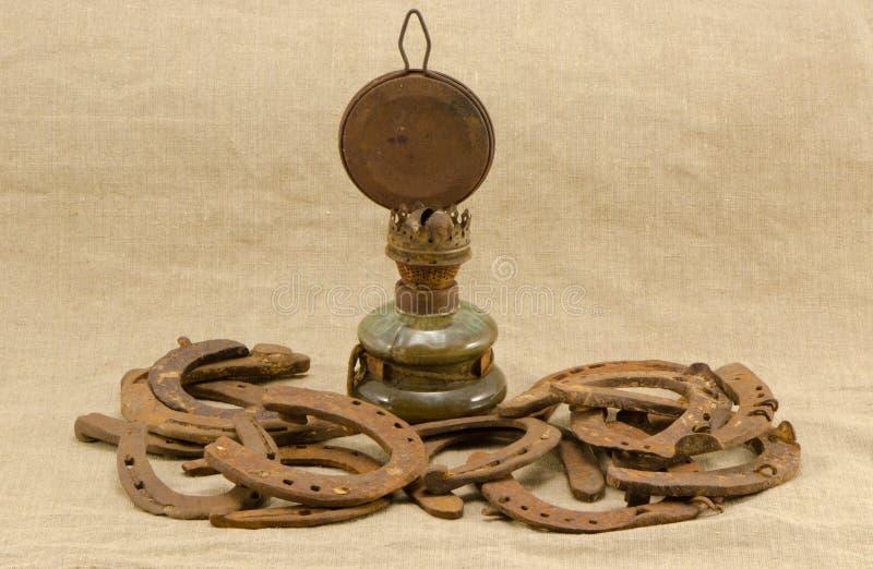 O cavalo oxidado retro da lâmpada de querosene calç o linho fotografia de stock
