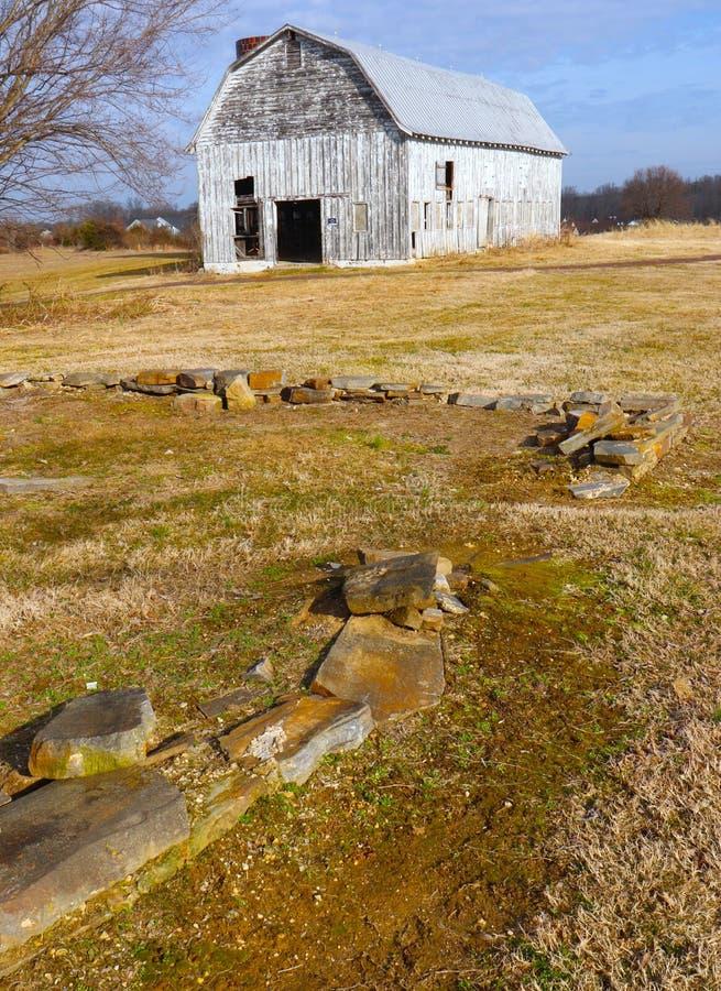 O celeiro abandonado velho senta-se entre as relíquias de pedra de um passado do tempo fotos de stock