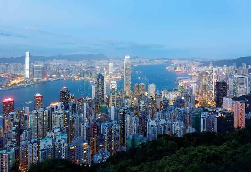 O cenário da noite de Hong Kong viu da parte superior de Victoria Peak com a skyline da cidade de arranha-céus aglomerados fotografia de stock royalty free