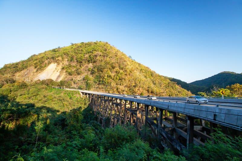 O cenário da ponte das montanhas do urso no crepúsculo, por do sol dourado brilha na condução de carros através da ponte e da cor fotografia de stock