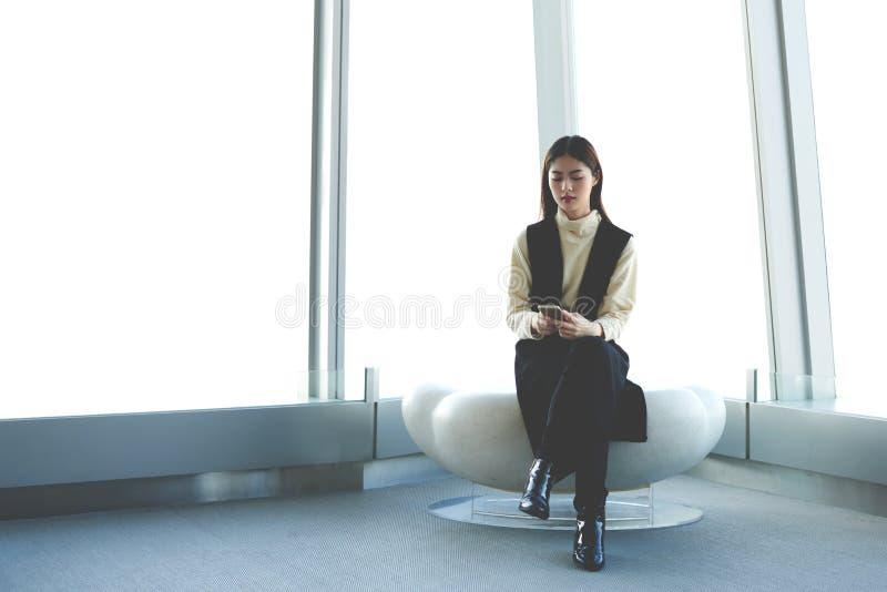 O CEO da mulher com o telefone de pilha nas mãos está sentando-se no interior moderno do escritório contra a janela do arranha-cé fotos de stock