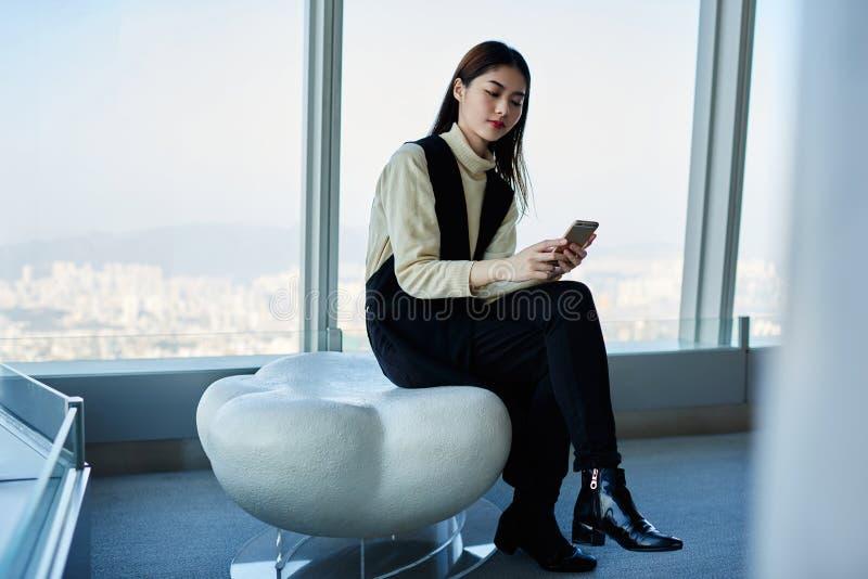 O CEO orgulhoso da mulher japonesa nova está verificando o email na rede através do telefone esperto imagens de stock