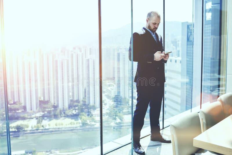 O CEO sério novo do homem no terno está pedindo o carro em linha para a viagem de negócios através do telefone de pilha fotografia de stock