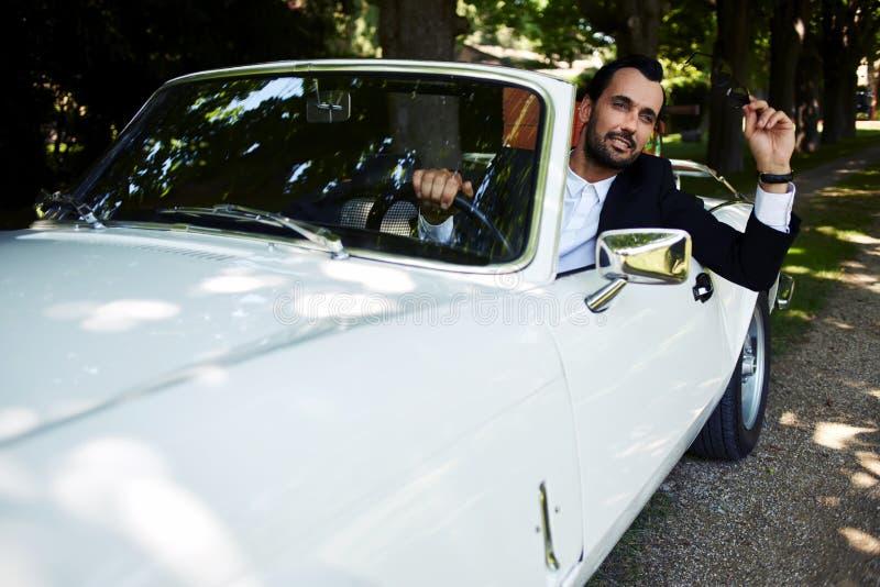 O certo e homem considerável seguro senta-se em seu carro convertível novo que olha fora tão feliz fotos de stock
