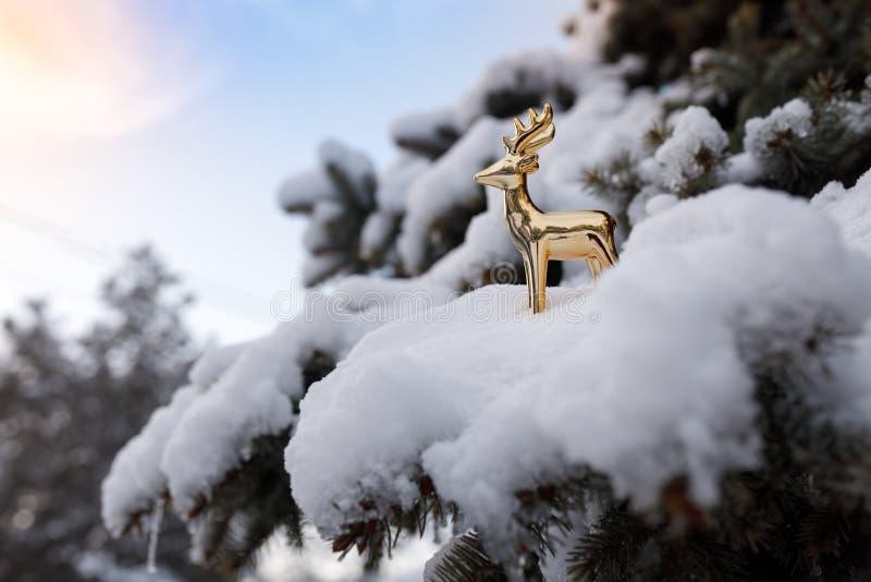 O cervo dourado do brinquedo está em um ramo nevado do pinho sempre-verde no céu azul do fundo fotografia de stock royalty free