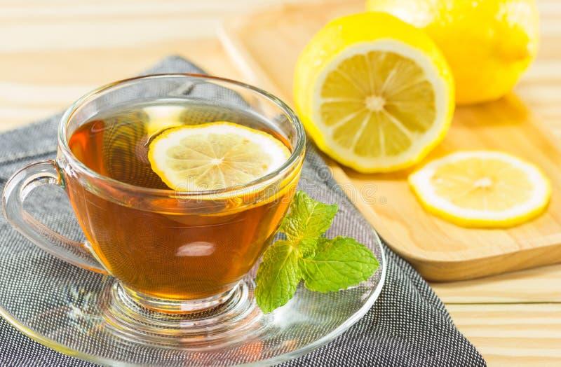 O chá com hortelã e limão no fundo de madeira, tonificação morna, selecti fotografia de stock royalty free