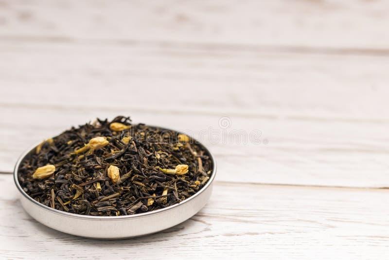 O chá com jasmim floresce na placa na tabela de madeira foto de stock