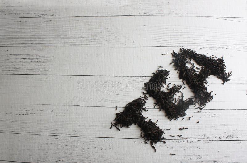 O CHÁ da palavra fez das folhas de chá no fundo de madeira branco foto de stock