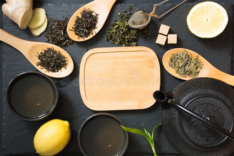 O chá japonês e chinês verde com alimento tradicional ajustou-se na tabela preta Vista superior com espaço da cópia fotografia de stock