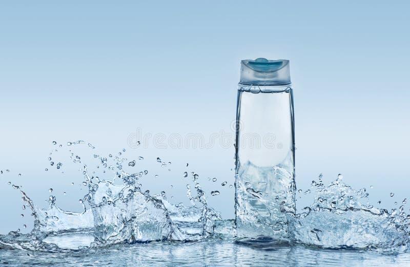 O champô hidratando no fundo da água azul com muitos grandes espirra em torno da garrafa fotos de stock royalty free