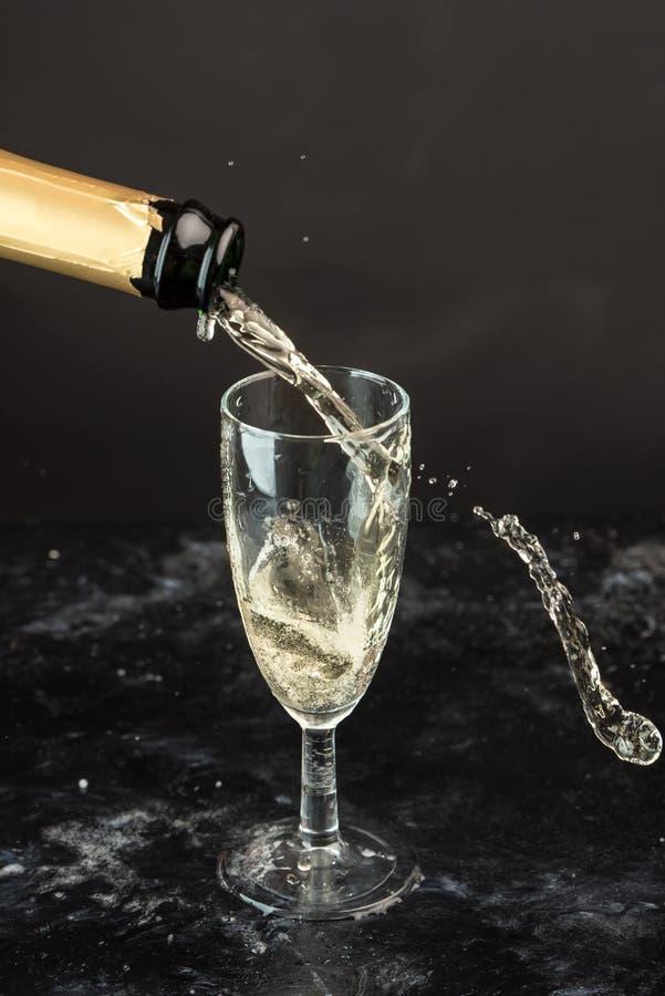 O champanhe dourado derramou de uma garrafa em umas gotas de vidro, visíveis, em bolhas e em um respingo imagens de stock royalty free