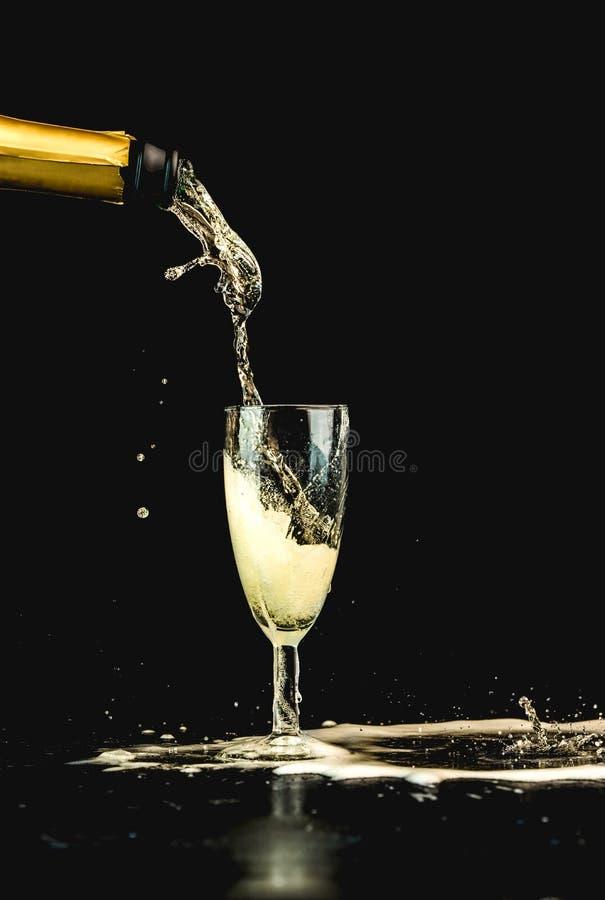 O champanhe dourado derramou de uma garrafa em umas gotas de vidro, visíveis, em bolhas e em um respingo imagens de stock