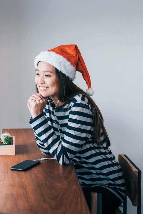 O chapéu asiático e o sorriso de Santa do desgaste do adolescente enfrentam o descanso de seu qui imagem de stock royalty free