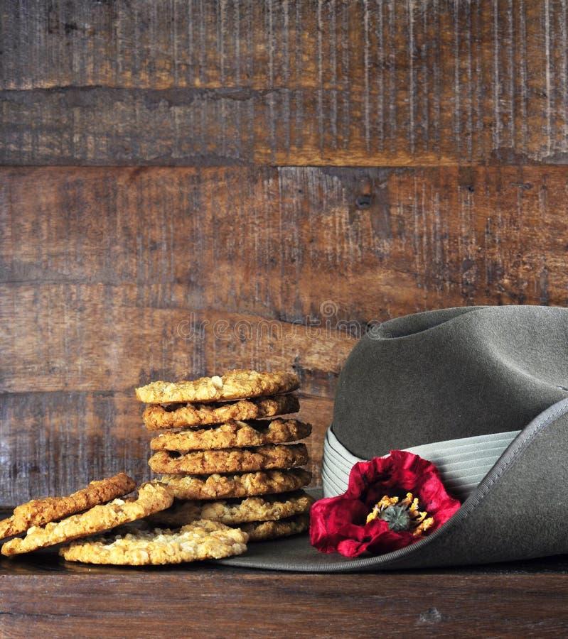 O chapéu de slouch australiano do exército e os biscoitos tradicionais de Anzac na obscuridade reciclaram a madeira imagens de stock royalty free