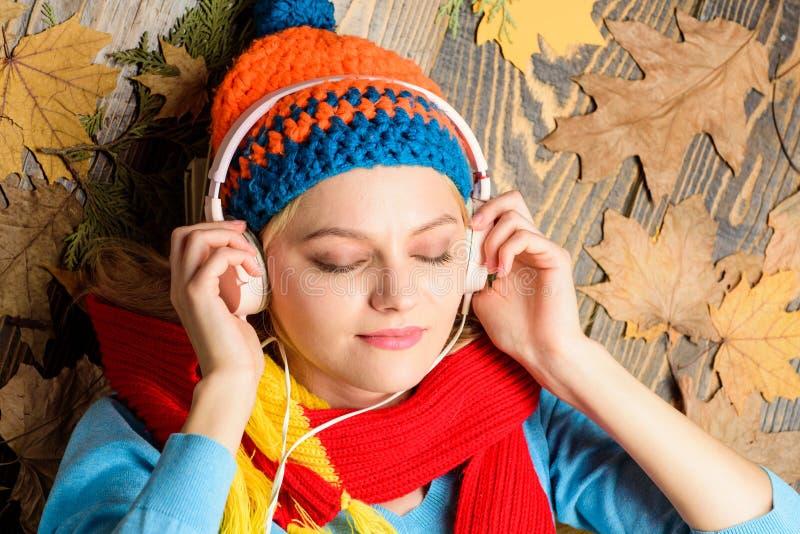 O chapéu e o lenço feitos malha mulher do moderno escutam fones de ouvido da música A configuração alegre da cara da menina no fu imagem de stock royalty free