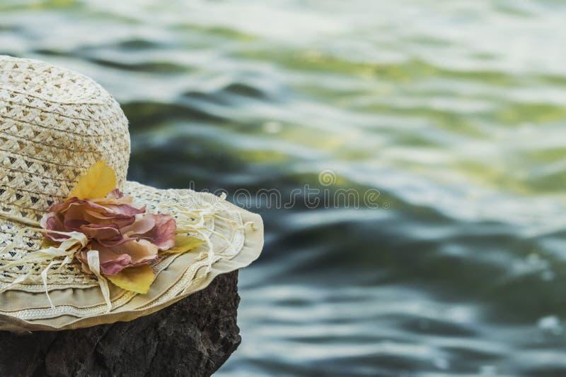 O chapéu ensolarado com flores encontra-se em uma rocha na frente do mar, tonificado fotos de stock