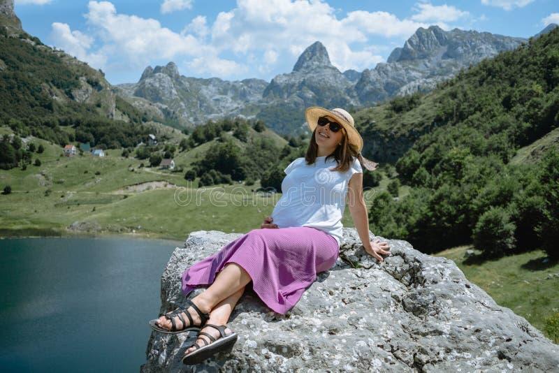 O chapéu vestindo da mulher gravida senta-se em uma grande rocha no backgroun fotografia de stock royalty free