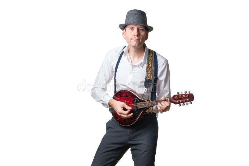 O chapéu vestindo do homem é concentrado que joga o bandolim fotos de stock