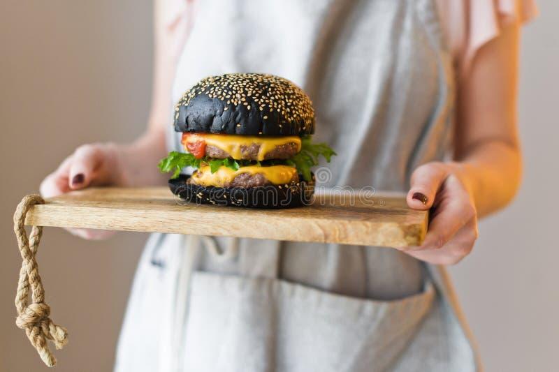 O chefe est? guardando uma placa de corte de madeira com um hamburguer preto foto de stock royalty free