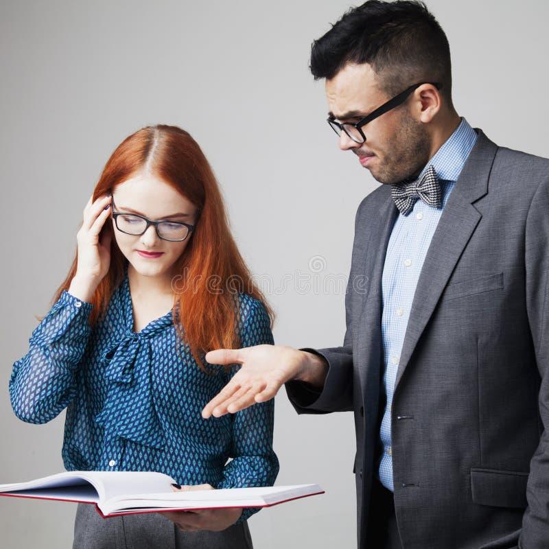 O chefe irritado irritado em um empregado e em uma ela novos é negócio chocado, fotografia de stock royalty free