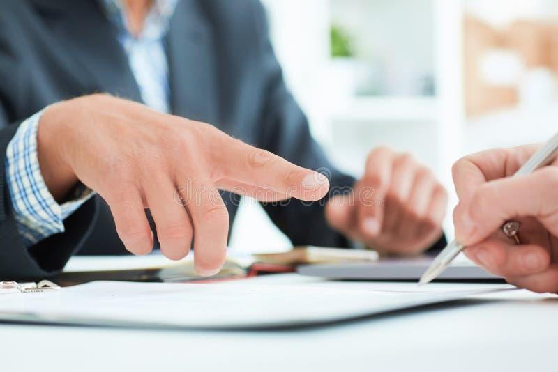 O chefe masculino recomenda que seu sinal do empregado um contrato no escritório O homem de negócio aponta ao lugar onde está fotos de stock