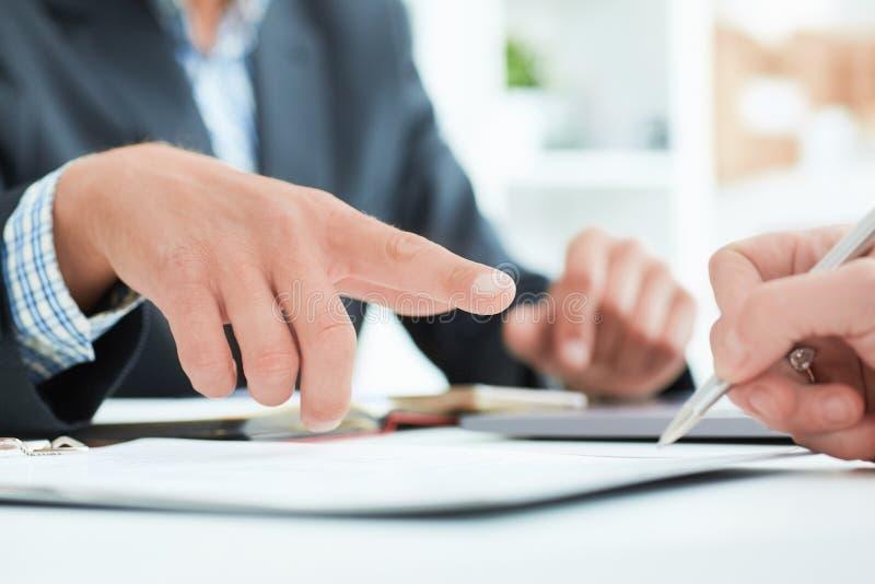 O chefe masculino recomenda que seu sinal do empregado um contrato no escritório O homem de negócio aponta ao lugar onde está foto de stock