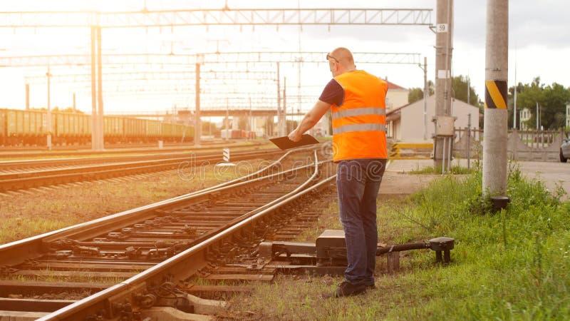 O chefe mau na estrada de ferro inspeciona o mecanismo da estrada de ferro do interruptor e grita no telefone foto de stock royalty free