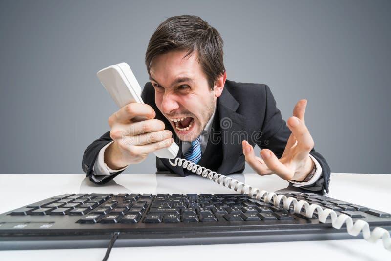 O chefe ou o gerente irritado estão chamando e gritarias ao telefone foto de stock