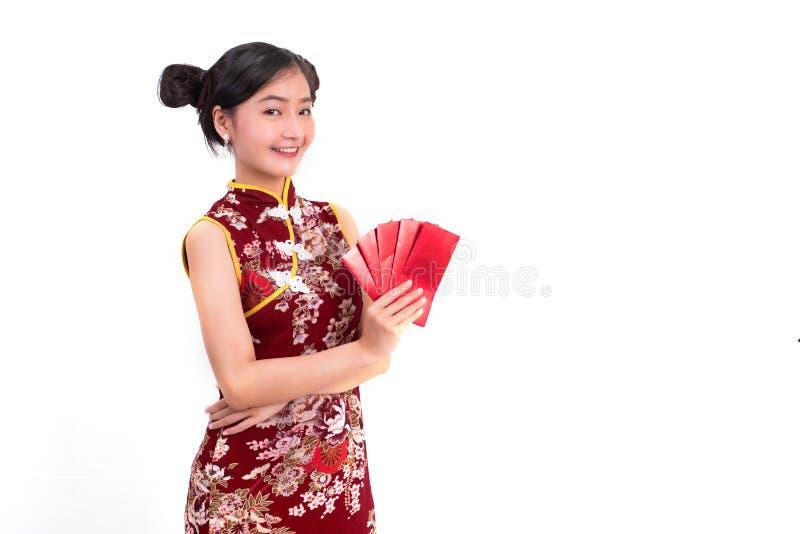 O cheongsam da mulher asiática nova da beleza e o pacote vestindo guardar de dinheiros gesticulam no evento chinês do festival do foto de stock