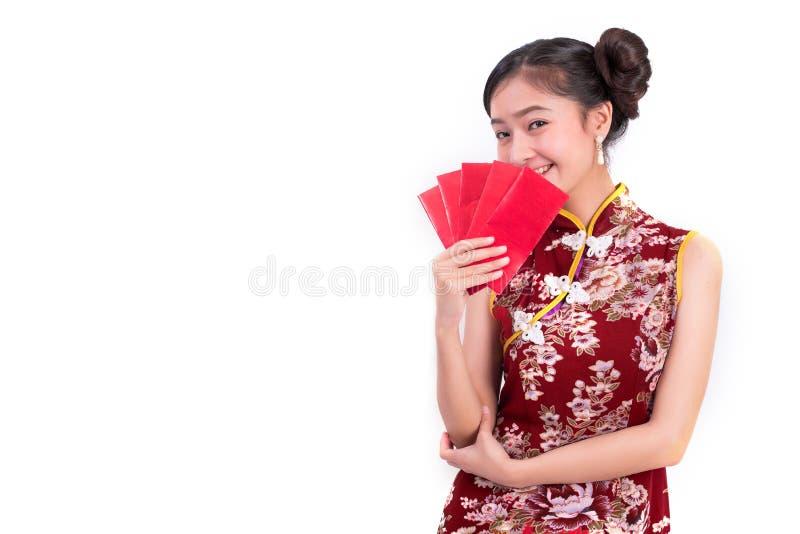 O cheongsam da mulher asiática nova da beleza e o pacote vestindo guardar de dinheiros gesticulam no evento chinês do festival do imagens de stock royalty free