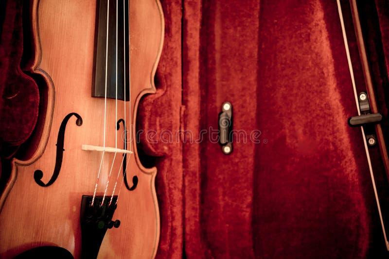 O chifre da m?sica ajustou 3 Fim acima do violino e curva em escuro aberto - caixa vermelha fotografia de stock royalty free