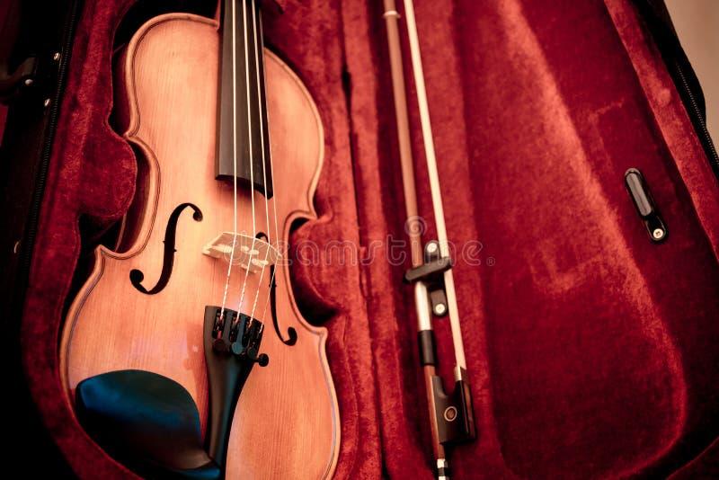 O chifre da m?sica ajustou 3 Fim acima do violino e curva em escuro aberto - caixa vermelha fotografia de stock