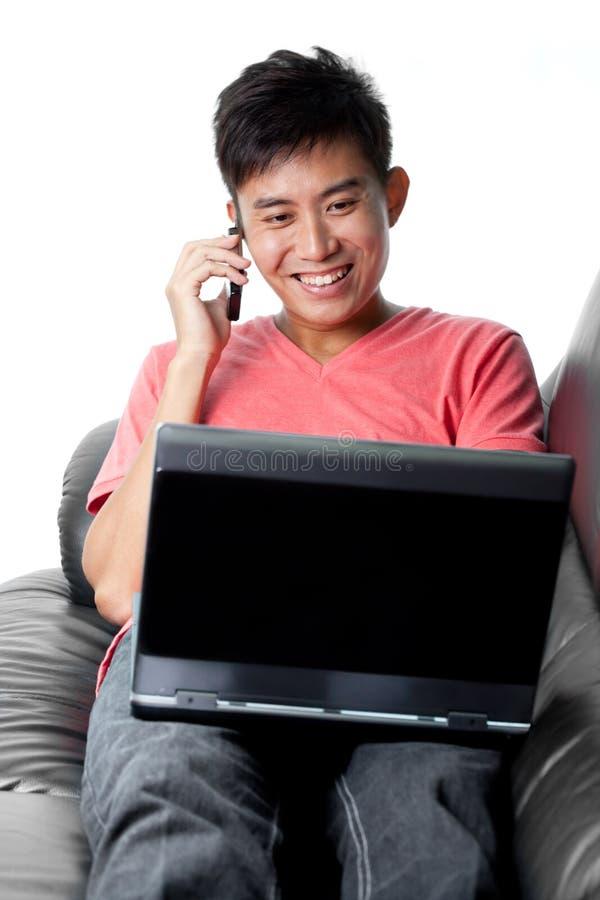 O chinês asiático novo surfa a rede e conversa no telefone foto de stock royalty free