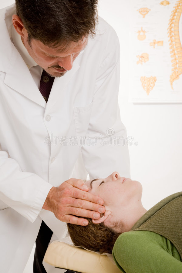 O Chiropractor ajusta a garganta do paciente foto de stock