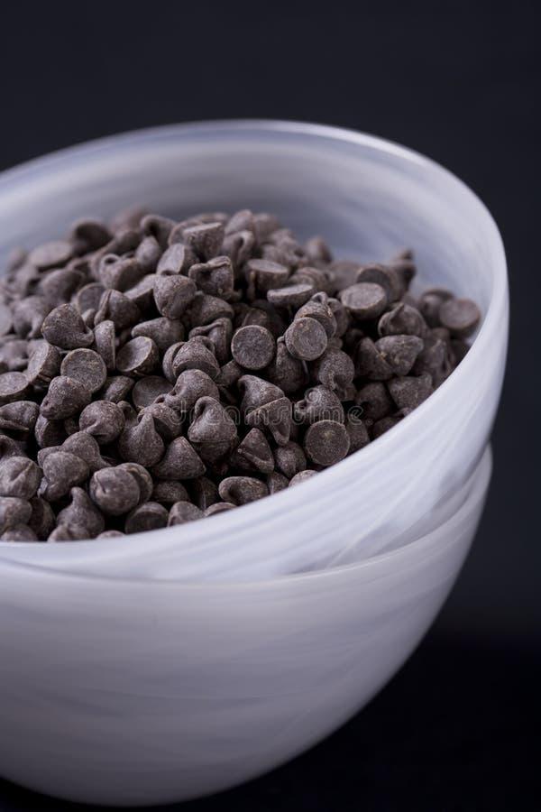 O chocolate do Vegan lasca dentro o vertical branco da bacia foto de stock royalty free