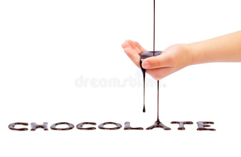 O chocolate líquido derrama da mão de uma criança em um branco foto de stock royalty free