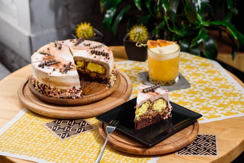 O chocolate mergulhou o bolo com enchimento amarelo e o esmalte bonito do café, decorados com tubules e grânulos da pastelaria imagem de stock