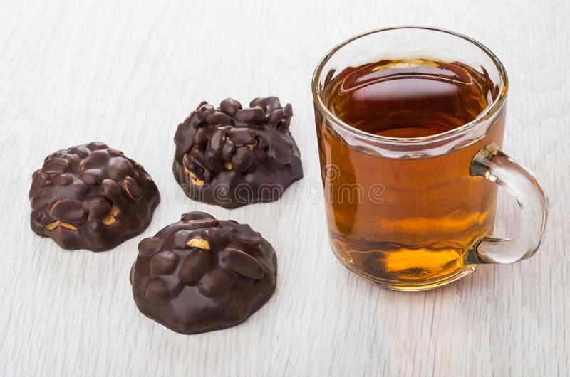 O chocolate vitrificou cookies com amendoins, copo transparente com chá imagens de stock royalty free
