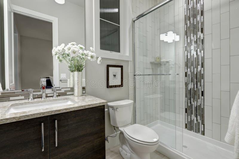 O chuveiro das pessoas sem marcação de vidro em um banheiro da casa luxuosa imagem de stock