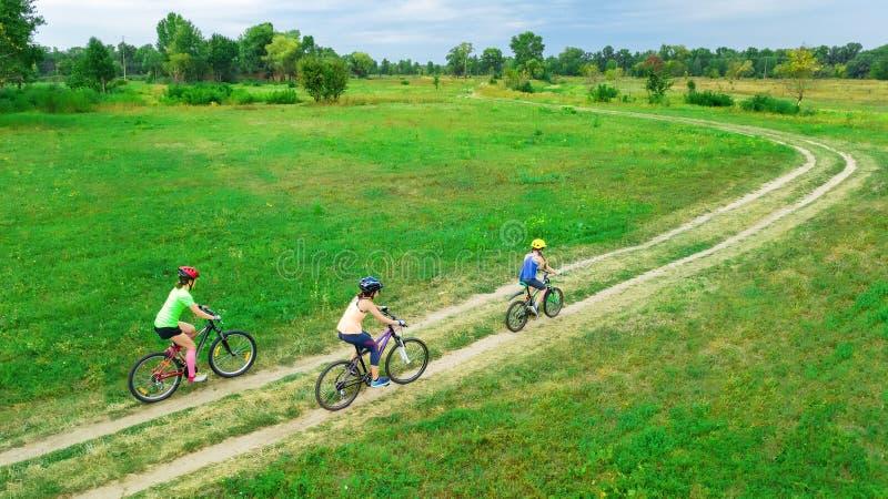 O ciclismo da família das bicicletas na opinião aérea fora de cima de, mãe ativa feliz com crianças tem o divertimento fotografia de stock royalty free