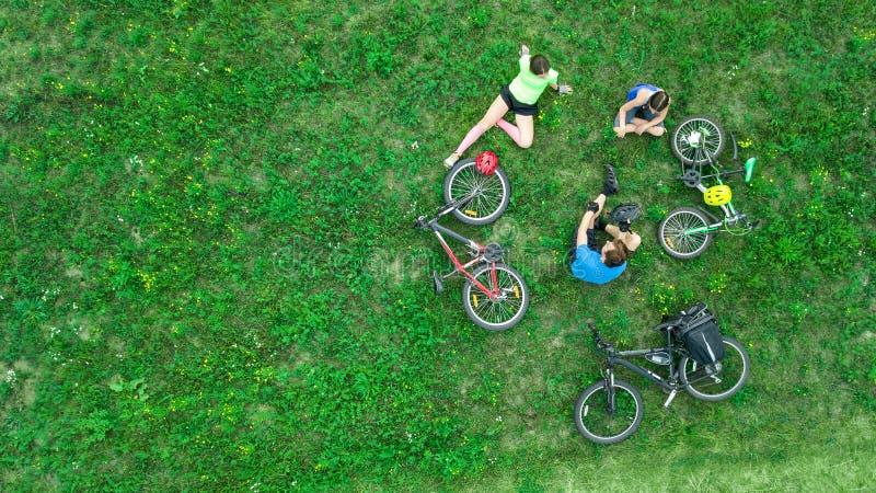 O ciclismo da família das bicicletas na opinião aérea fora de cima de, pais ativos com criança tem o divertimento e relaxa na gra fotografia de stock