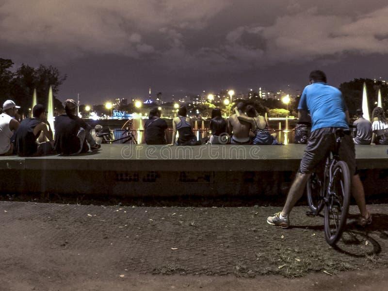 O ciclista e a skyline da cidade em Ibirapuera estacionam na noite foto de stock