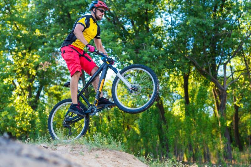 O ciclista em um t-shirt brilhante amarelo está montando da parte superior, um estilo de vida ativo imagem de stock