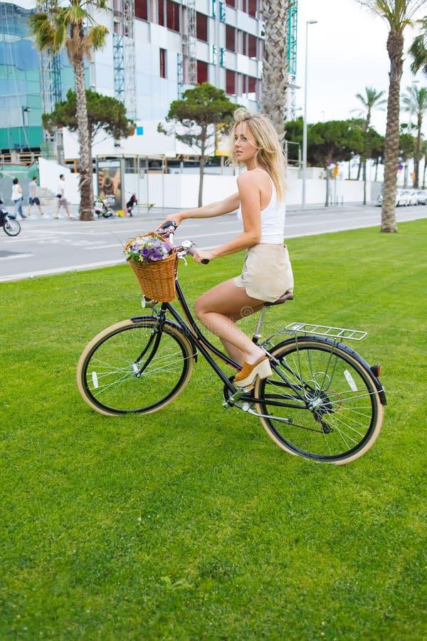 O ciclista encantador da jovem mulher aprecia o ridingin o parque em sua bicicleta do vintage com uma cesta das flores imagens de stock