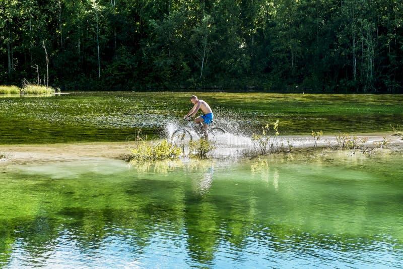 O ciclista monta uma bicicleta através do rio no baixio fotografia de stock