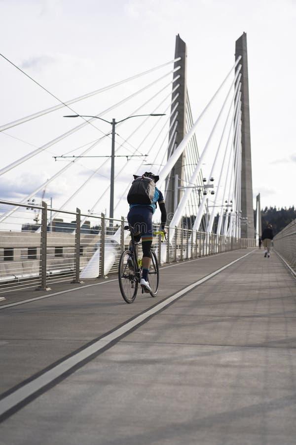 O ciclista na bicicleta da estrada está montando a ponte de cruzamento de Tilikum foto de stock