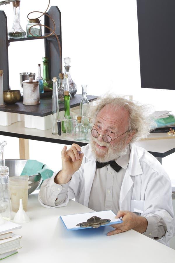 O cientista amigável no laboratório faz anotações na prancheta fotos de stock royalty free